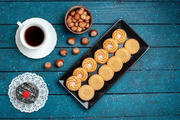 Widok z góry na herbatę z orzechami i ciasteczkami na rustykalnym niebieskim biurku z cukrowym ciastkiem