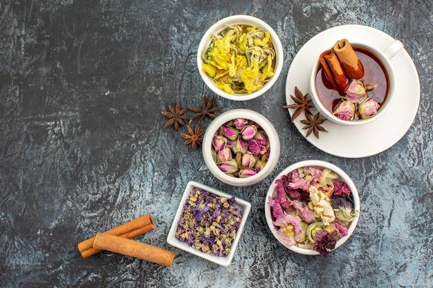 Widok z góry na herbatę ziołową z cynamonem i suchymi kwiatami na szarym tle