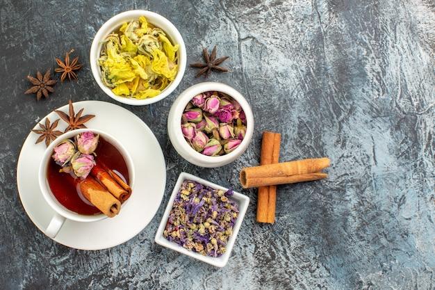 Widok z góry na herbatę ziołową z trzema miskami suchego kwiatu i laskami cynamonu na szarym tle