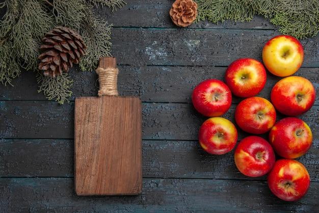Widok z góry na jabłka i deskę dziewięć jabłek i deska do krojenia pod gałęziami drzew z szyszkami