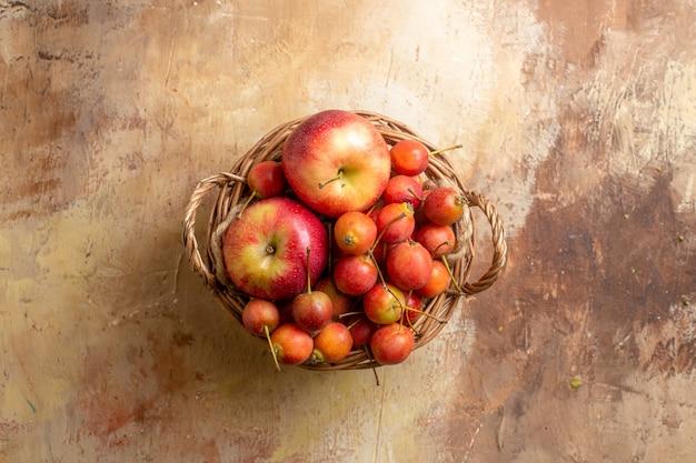 Widok z góry na jagody drewniany kosz z jagodami i jabłkami na kremowym stole