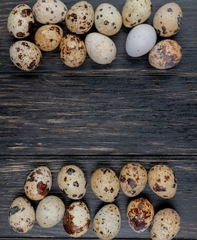 Widok z góry na jaja przepiórcze z kremowymi skorupkami z brązowymi plamami ułożonymi na drewnianym tle z miejsca na kopię