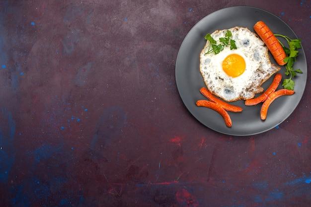 Widok z góry na jajecznicę z zieleniną i kiełbasą wewnątrz talerza na ciemnej powierzchni