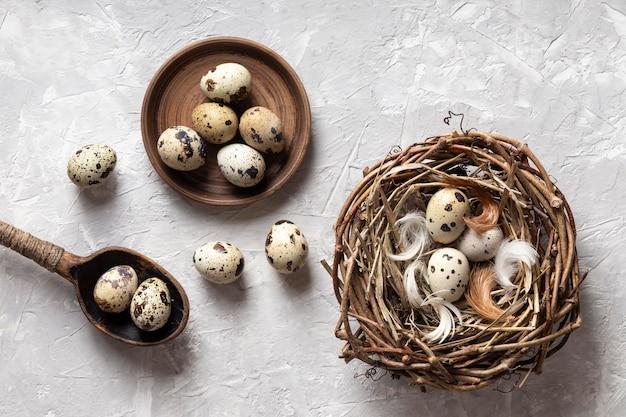 Widok z góry na jajka na wielkanoc z drewnianą łyżką i ptasie gniazdo