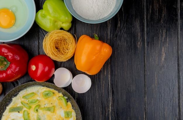 Widok z góry na jajka sadzone ze skorupkami jaj z kolorową papryką na drewnianym tle z miejsca na kopię