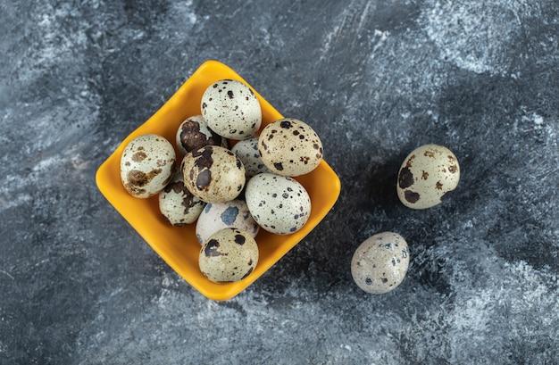 Widok z góry na jajko przepiórcze w gospodarstwie ekologicznym. na szarym stole.