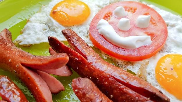 Widok z góry na jajko sadzone i kiełbaski na zielonym talerzu, serwujący śniadanie dla dziecka.