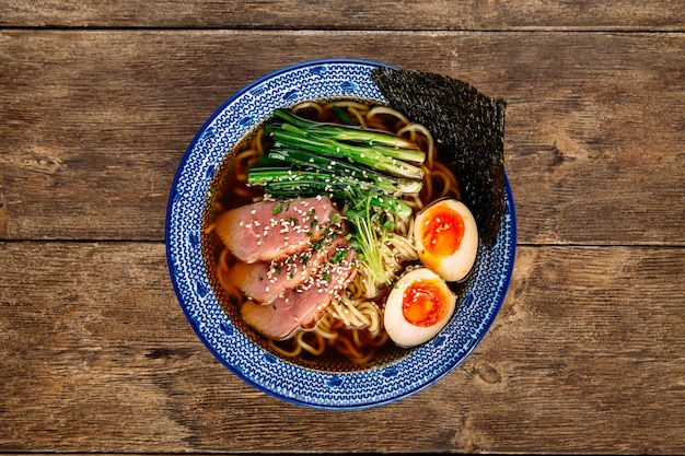 Widok z góry na japońską zupę z makaronem ramen z jajkami pastrami i ajitama