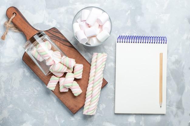 Widok z góry na jasnobiałym biurku, kolorowe pyszne pianki marshmallows, małe cukierki.