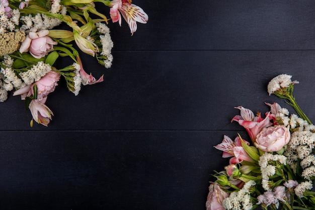 Widok z góry na jasnoróżowe kwiaty na czarnej powierzchni