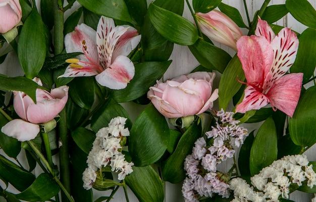 Widok z góry na jasnoróżowe kwiaty z liśćmi na szarej powierzchni