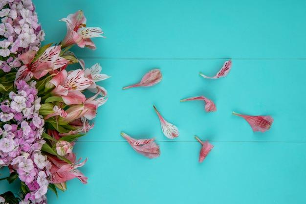 Widok z góry na jasnoróżowe kwiaty z płatkami na jasnoniebieskiej powierzchni