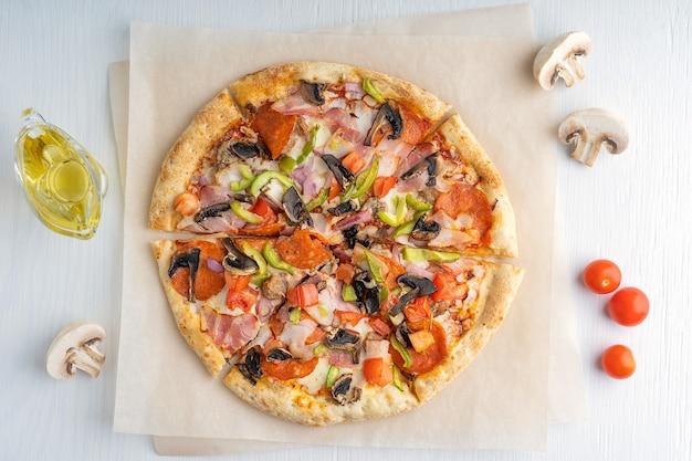 Widok z góry na jedną pokrojoną smaczną włoską pizzę z pieczarkami, pomidorami, szynką, pieprzem i serem