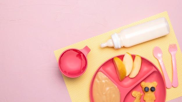 Widok z góry na jedzenie dla niemowląt na talerzu z butelką dla niemowląt