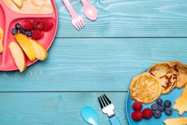 Widok z góry na jedzenie dla niemowląt z jagodami i sztućcami