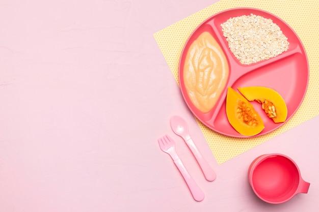 Widok z góry na jedzenie dla niemowląt z owocami i sztućcami