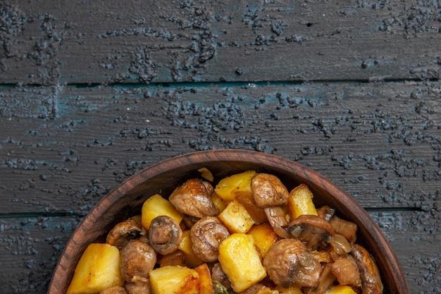 Widok z góry na jedzenie na stole brązowa miska z ziemniakami i grzybami na dole stołu