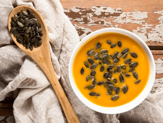Widok z góry na jesienną zupę dyniową z nasionami i drewnianą łyżką