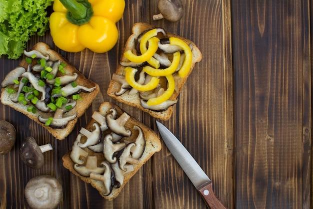Widok z góry na kanapki z grzybami shiitake i warzywami na brązowym drewnianym
