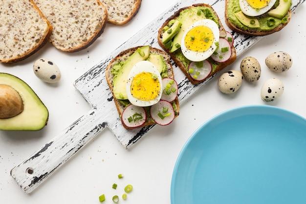 Widok z góry na kanapki z jajkiem i awokado na stole z płytą