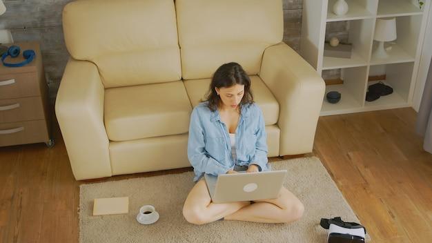 Widok z góry na kaukaską kobietę piszącą e-mail siedzącą na podłodze w swoim przytulnym, jasnym domu