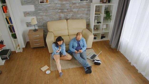 Widok z góry na kaukaską parę w dżinsach przeglądających na smartfonie na podłodze ich mieszkania