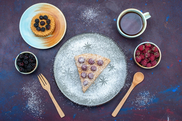 Widok z góry na kawałek ciasta pyszne z malinami i herbatą na ciemnej powierzchni
