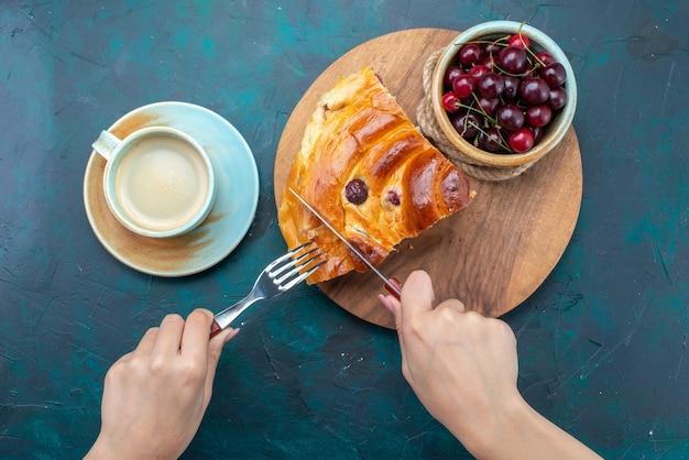 Widok z góry na kawałek ciasta wiśniowego z mlekiem i świeżymi wiśniami na ciemnoniebieskim, ciasto do pieczenia słodkich owoców