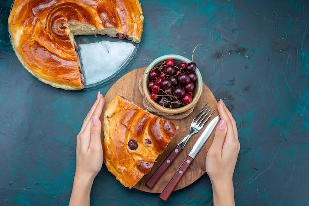 Widok z góry na kawałek ciasta wiśniowego ze świeżymi wiśniami i mlekiem na ciemnej, słodkiej herbacie z ciasta owocowego