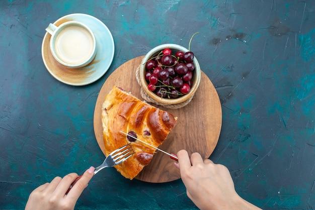 Widok z góry na kawałek ciasta wiśniowego ze świeżymi wiśniami na ciemnoniebieskim, ciastko owocowe do pieczenia słodkiej herbaty