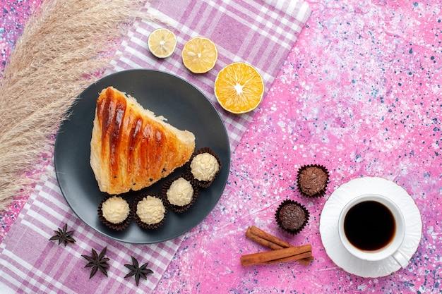 Widok z góry na kawałek ciasta z cynamonową filiżanką herbaty i cukierków czekoladowych na różowej powierzchni