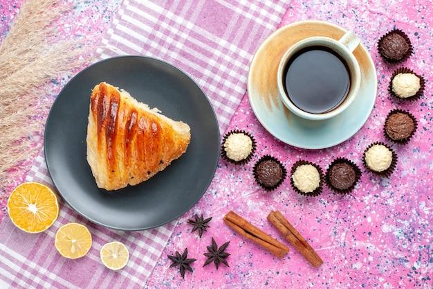 Widok z góry na kawałek ciasta z filiżanką herbaty i cukierków czekoladowych na jasnoróżowej powierzchni