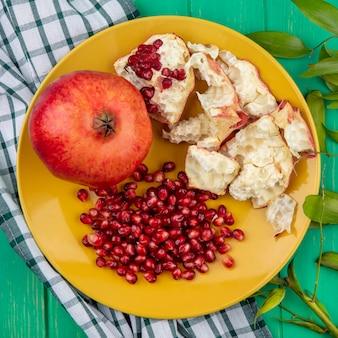 Widok z góry na kawałki granatu, skorupki jagód i całość w talerzu na kraciastej tkaninie i zielonej powierzchni ozdobionej liśćmi