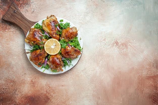 Widok z góry na kawałki kurczaka kurczaka z ziołami, cebulą cytrynową na lawaszu na pokładzie