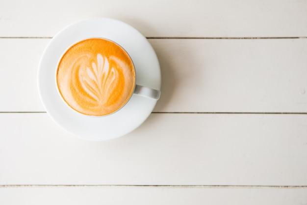 Widok z góry na kawę latte lub kawę cappuccino w białej filiżance z latte art na białym drewnianym stole.