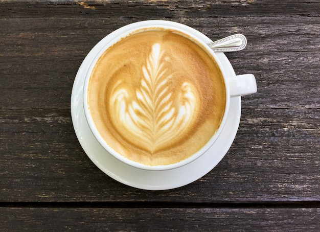 Widok z góry na kawę latte lub kawę cappuccino w białej filiżance z latte art na drewnianym stole.