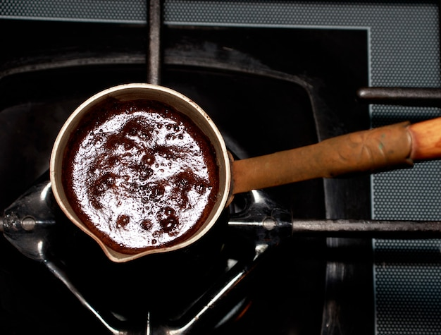Widok z góry na kawę parzoną w miedzianym turku według dawnych tradycji i receptur.