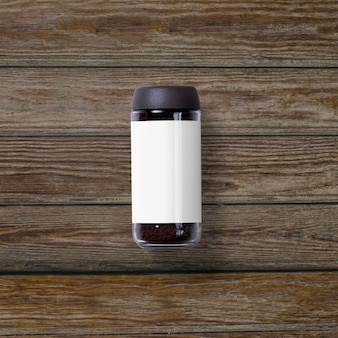 Widok z góry na kawę rozpuszczalną w słoiku na białym tle na drewnianym tle
