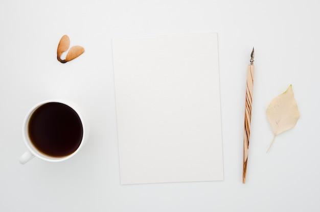 Widok z góry na kawę z papierem i jesiennymi liśćmi