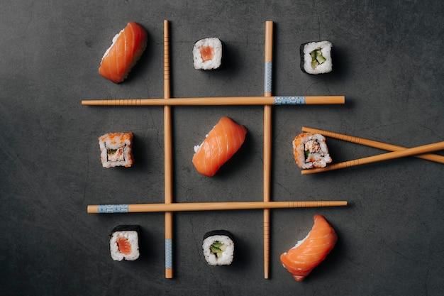 Widok z góry na kilka japońskich rolek sushi i kilka kawałków łososia z ryżem o bardzo oryginalnym kształcie i ułożonych jak trzy na rusztach z pałeczkami.