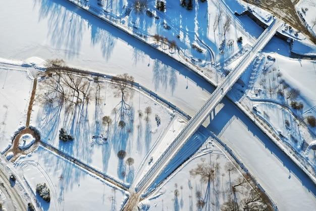 Widok z góry na kładkę dla pieszych nad zamarzniętą rzeką świsłocz w mińsku. białoruś.