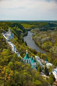 Widok z góry na klasztory i pensjonaty położone nad brzegiem rzeki w leśnych zaroślach
