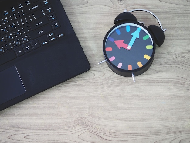 Widok z góry na klawiaturę laptopa i retro analogowy zegar w stylu vintage na drewnianym stole!