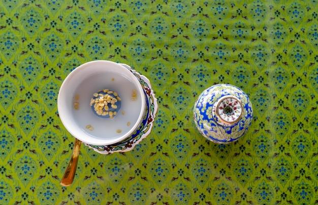 Widok z góry na knedle z cukrem w kremie z mleka kokosowego lub tajskim tradycyjnym deserze zwanym kanom ko, posypane paloną ภłuskaną zieloną fasolą na stole