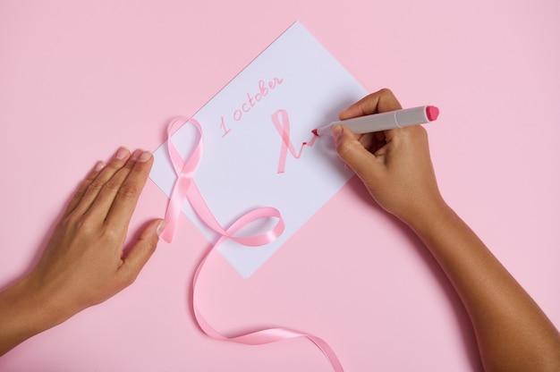 Widok z góry na kobiecą rękę trzymającą pisak pisze 1 października i rysuje na papierze różowy symbol miesiąca świadomości raka piersi, różową wstążkę z niekończącym się końcem leżącą na różowym tle