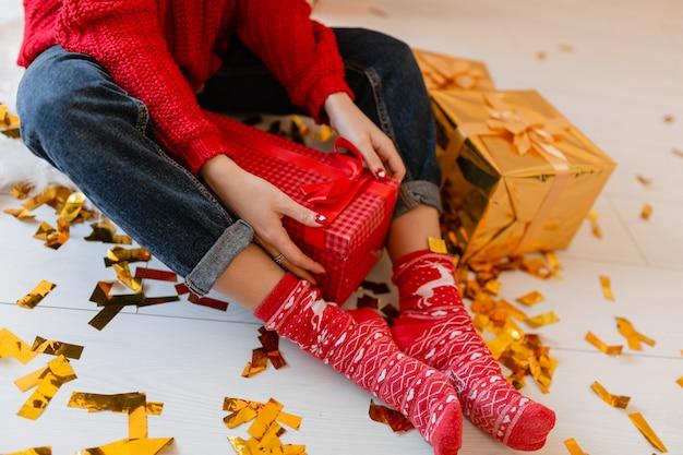 Widok z góry na kobietę w czerwonych skarpetkach siedzącą w domu na boże narodzenie na złotym konfetti, rozpakowywanie peresentów i pudełek prezentowych