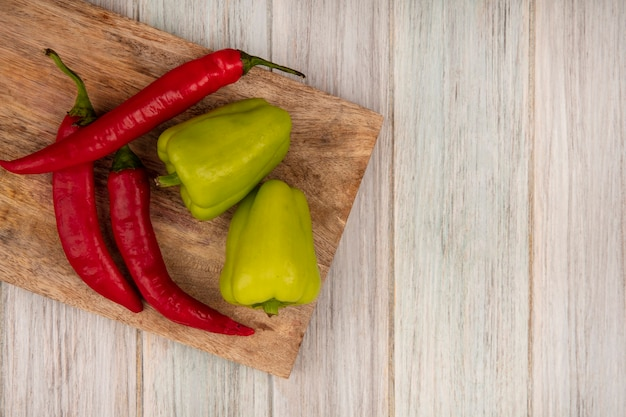 Widok z góry na kolorowe papryki bell i chili na drewnianej desce kuchennej na szarym tle drewnianych z miejsca na kopię