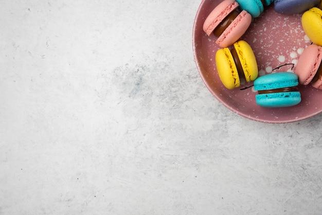 Widok z góry na kolorowe pastelowe makaroniki na białym tle.