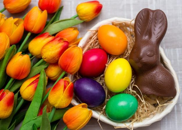 Widok z góry na kolorowe pisanki, czekoladowe króliczki i kwiaty tulipanów na stole