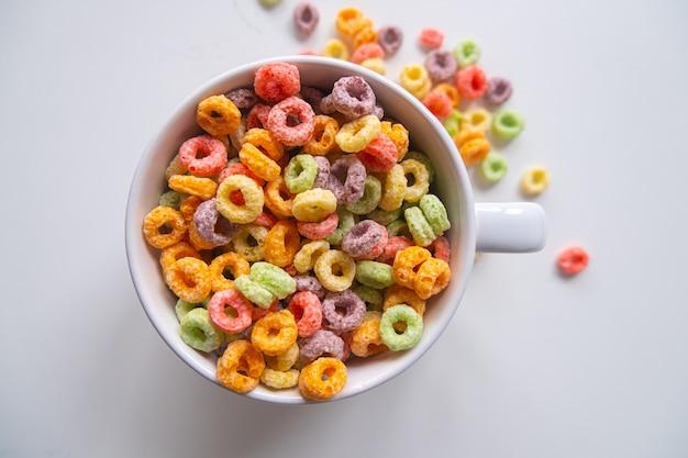 Widok z góry na kolorowe płatki śniadaniowe w białej misce.